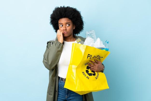Jonge afro-amerikaanse vrouw met een kringloopzak geïsoleerd op kleurrijke achtergrond nerveus en bang handen op de mond