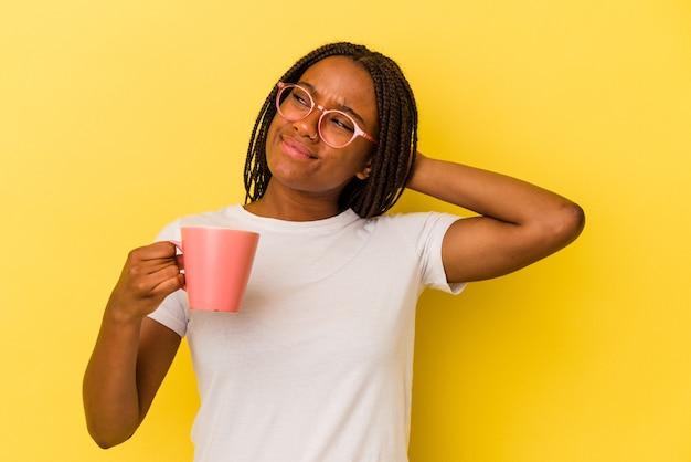 Jonge afro-amerikaanse vrouw met een mok geïsoleerd op een gele achtergrond die de achterkant van het hoofd aanraakt, denkt en een keuze maakt.