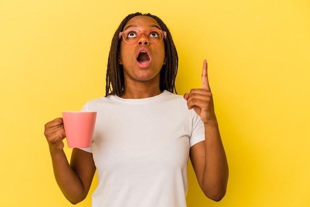 Jonge afro-amerikaanse vrouw met een mok geïsoleerd op een gele achtergrond die ondersteboven wijst met geopende mond.