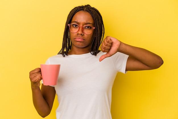 Jonge afro-amerikaanse vrouw met een mok geïsoleerd op een gele achtergrond met een afkeer gebaar, duim omlaag. onenigheid begrip.