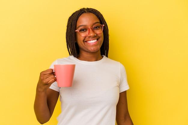 Jonge afro-amerikaanse vrouw met een mok geïsoleerd op gele achtergrond gelukkig, glimlachend en vrolijk.