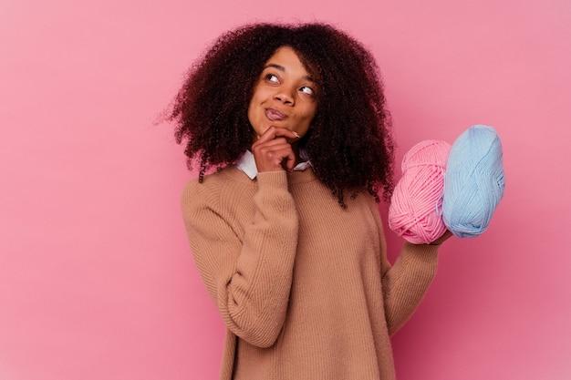 Jonge afro-amerikaanse vrouw met een naaigaren geïsoleerd op roze zijwaarts kijkend met twijfelachtige en sceptische uitdrukking.