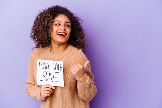 Jonge afro-amerikaanse vrouw met een plakkaat gemaakt met liefde geïsoleerd op paarse achtergrond punten met duim vinger weg, lachen en zorgeloos.