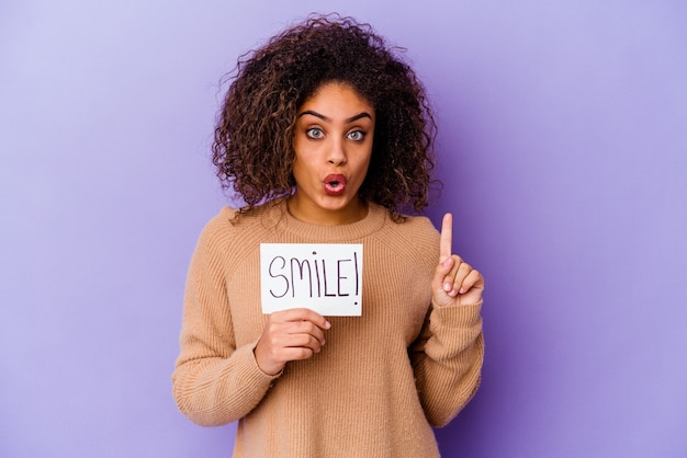 Jonge afro-amerikaanse vrouw met een plakkaat met glimlach geïsoleerd op paarse achtergrond met een geweldig idee, concept van creativiteit.