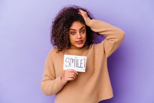 Jonge afro-amerikaanse vrouw met een plakkaat met glimlach geïsoleerd op paarse muur wordt geschokt, ze heeft belangrijke vergadering herinnerd.