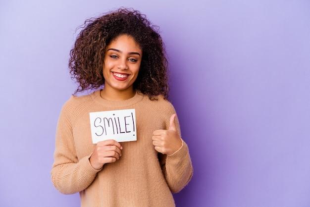 Jonge afro-amerikaanse vrouw met een plakkaat smile geïsoleerd op een paarse achtergrond glimlachend en duim omhoog