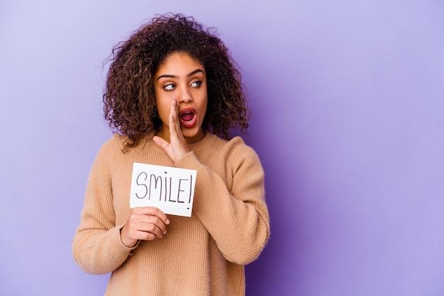 Jonge afro-amerikaanse vrouw met een plakkaat smile geïsoleerd op paarse achtergrond zegt een geheim heet remnieuws en kijkt opzij