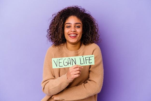 Jonge afro-amerikaanse vrouw met een plakkaat veganistisch geïsoleerd lachen en plezier maken.