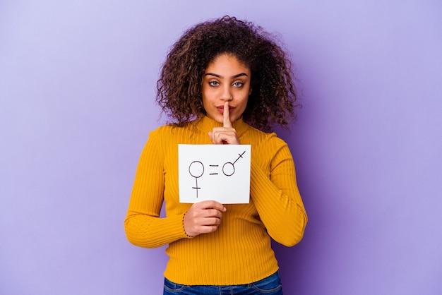 Jonge afro-amerikaanse vrouw met een plakkaat voor gendergelijkheid geïsoleerd op een paarse achtergrond die een geheim houdt of om stilte vraagt.