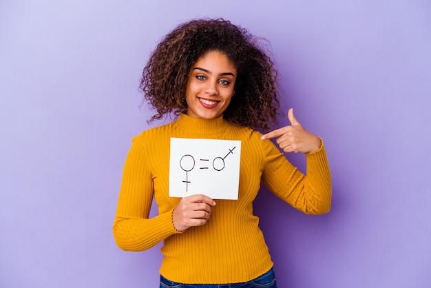 Jonge afro-amerikaanse vrouw met een plakkaat voor gendergelijkheid geïsoleerd op een paarse achtergrond persoon die met de hand wijst naar de ruimte van een shirtkopie, trots en zelfverzekerd