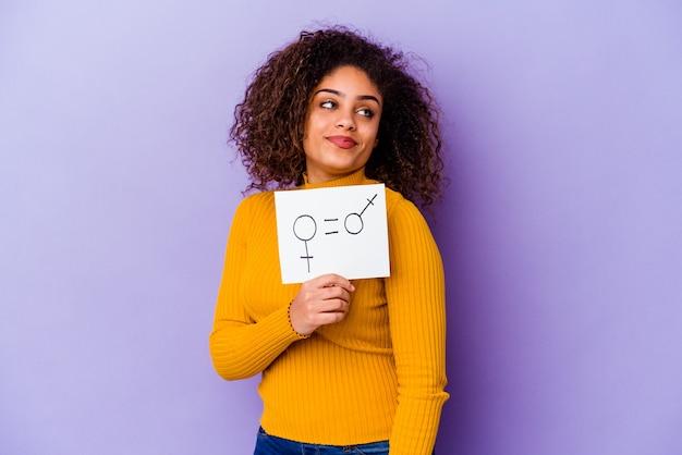 Jonge afro-amerikaanse vrouw met een plakkaat voor gendergelijkheid geïsoleerd op paarse achtergrond kijkt opzij glimlachend, vrolijk en aangenaam.