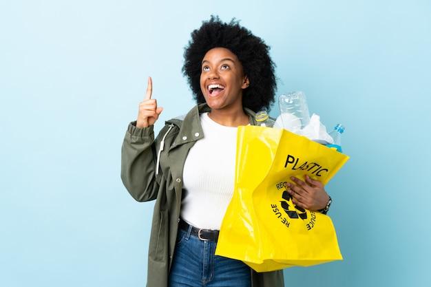 Jonge afro-amerikaanse vrouw met een recycle tas op kleurrijke muur omhoog en verrast