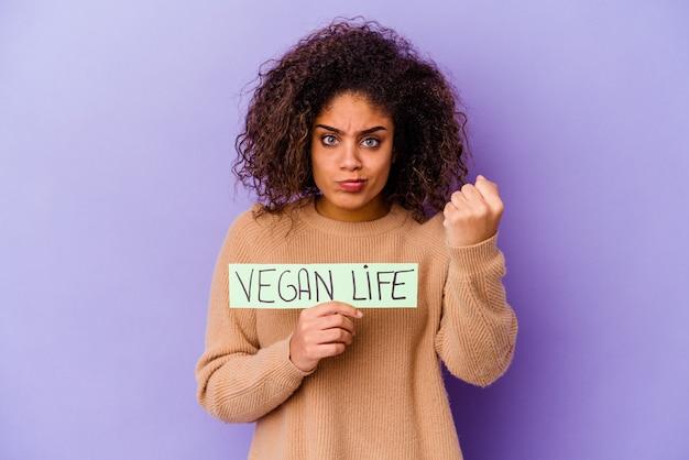 Jonge afro-amerikaanse vrouw met een veganistisch leven plakkaat geïsoleerd met vuist naar camera, agressieve gezichtsuitdrukking.