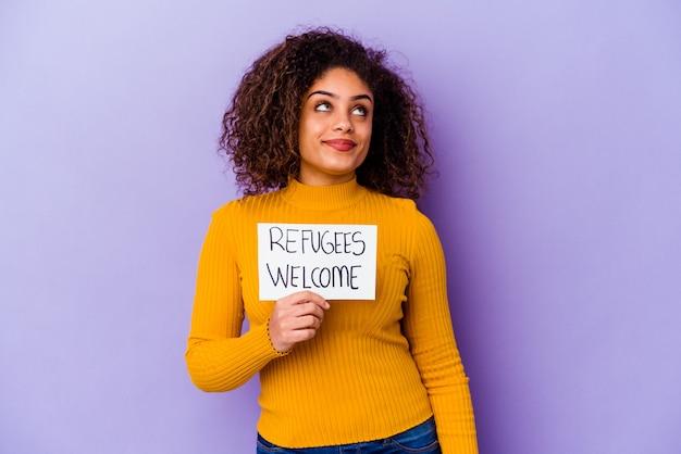 Jonge afro-amerikaanse vrouw met een vluchtelingen welkom plakkaat geïsoleerd dromen van het bereiken van doelen en doeleinden