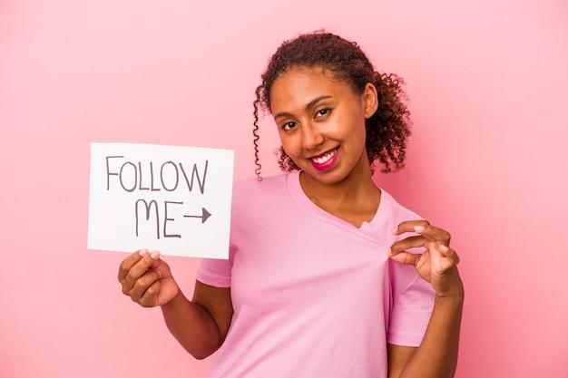 Jonge afro-amerikaanse vrouw met een volg mij plakkaat geïsoleerd op roze achtergrond