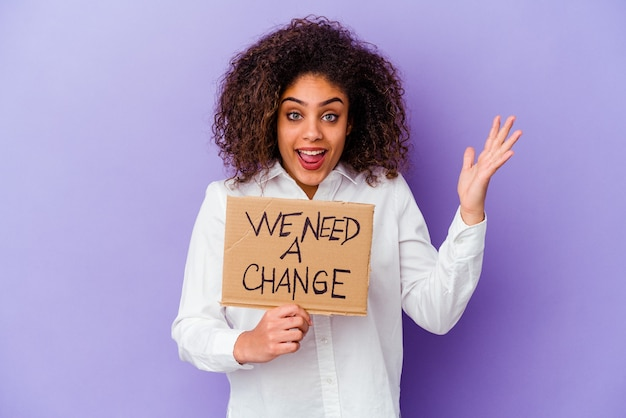 Jonge afro-amerikaanse vrouw met een we hebben een aanplakbiljet nodig dat op een paarse muur wordt geïsoleerd en een aangename verrassing ontvangt, opgewonden en handen opsteken.