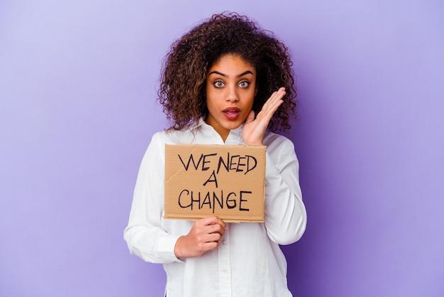 Jonge afro-amerikaanse vrouw met een we hebben een aanplakbiljet verandering nodig geïsoleerd op paarse muur verrast en geschokt.