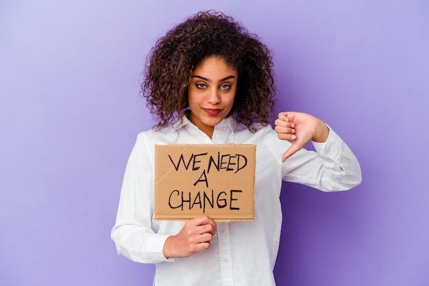 Jonge afro-amerikaanse vrouw met een we hebben een veranderingsbordje nodig geïsoleerd op een paarse achtergrond met een afkeergebaar, duim omlaag. onenigheid begrip.