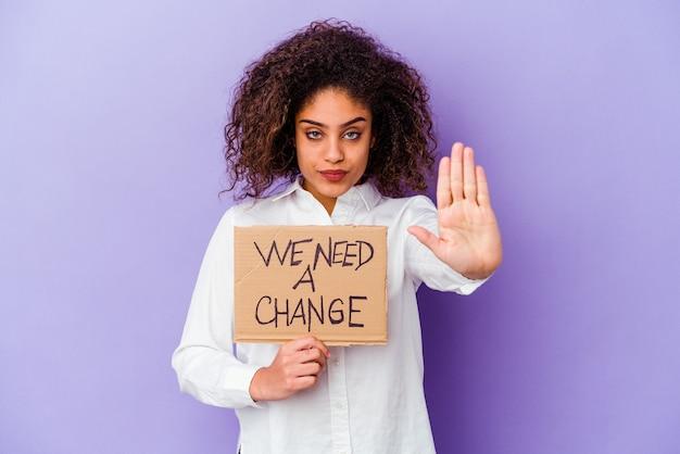 Jonge afro-amerikaanse vrouw met een we hebben een wijzigingsbordje nodig dat op een paarse achtergrond wordt geïsoleerd en met uitgestrekte hand een stopbord toont, waardoor je wordt voorkomen.