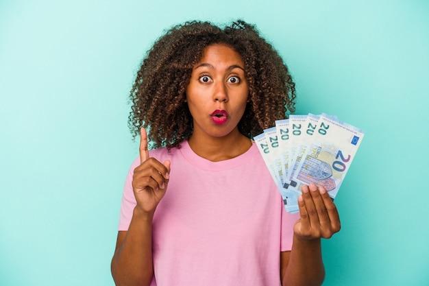 Jonge afro-amerikaanse vrouw met eurobankbiljetten geïsoleerd op blauwe achtergrond met een geweldig idee, concept van creativiteit.