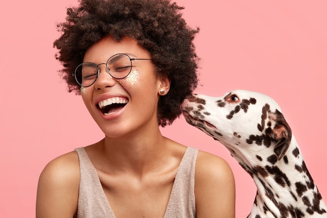Jonge afro-amerikaanse vrouw met glitters op gezicht en haar hond