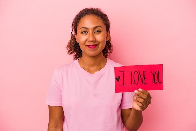 Jonge afro-amerikaanse vrouw met ik hou van je plakkaat geïsoleerd op roze achtergrond