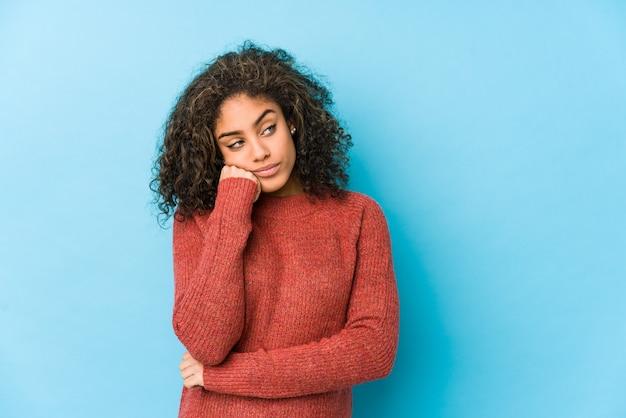 Jonge afro-amerikaanse vrouw met krullend haar die zich verdrietig en peinzend voelt, kijkend naar kopie ruimte.