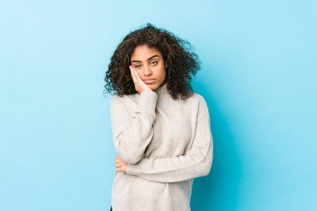 Jonge afro-amerikaanse vrouw met krullend haar die zich verveelt, vermoeid is en een ontspannen dag nodig heeft.