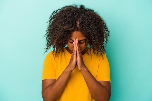 Jonge afro-amerikaanse vrouw met krullend haar geïsoleerd op blauwe achtergrond bidden, tonen toewijding, religieuze persoon op zoek naar goddelijke inspiratie.