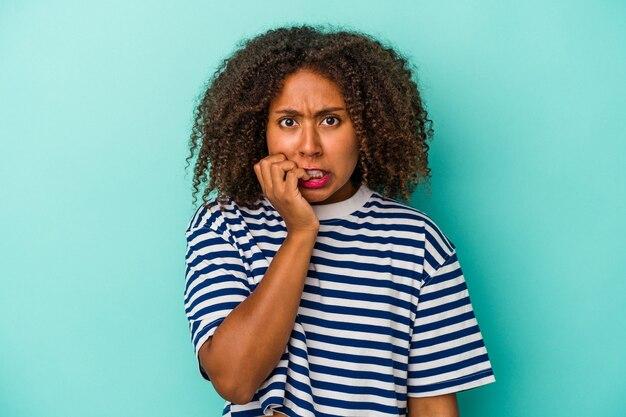 Jonge afro-amerikaanse vrouw met krullend haar geïsoleerd op blauwe achtergrond bijtende nagels, nerveus en erg angstig.