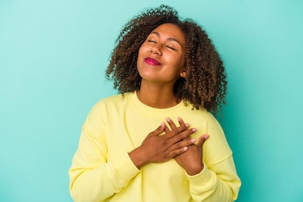 Jonge afro-amerikaanse vrouw met krullend haar geïsoleerd op blauwe achtergrond heeft vriendelijke uitdrukking, palm op borst drukken. liefdesconcept.