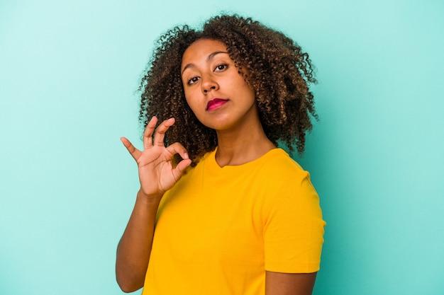 Jonge afro-amerikaanse vrouw met krullend haar geïsoleerd op blauwe achtergrond knipoogt en houdt een goed gebaar met de hand.