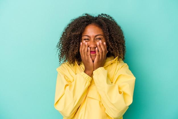 Jonge afro-amerikaanse vrouw met krullend haar geïsoleerd op blauwe achtergrond lachen om iets, mond bedekken met handen.