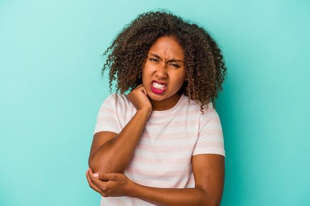 Jonge afro-amerikaanse vrouw met krullend haar geïsoleerd op blauwe achtergrond masseren elleboog, lijden na een slechte beweging.