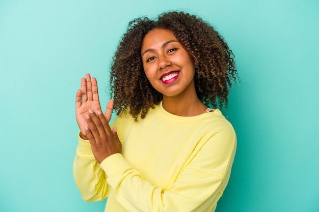Jonge afro-amerikaanse vrouw met krullend haar geïsoleerd op blauwe achtergrond voelt zich energiek en comfortabel, wrijft zelfverzekerd over de handen.