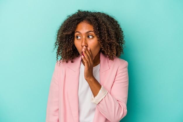 Jonge afro-amerikaanse vrouw met krullend haar geïsoleerd op blauwe achtergrond wordt geschokt vanwege iets dat ze heeft gezien.