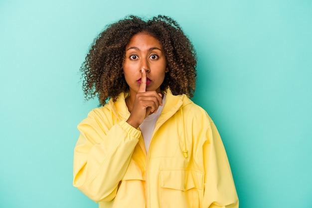 Jonge afro-amerikaanse vrouw met krullend haar geïsoleerd op een blauwe achtergrond die een geheim houdt of om stilte vraagt.