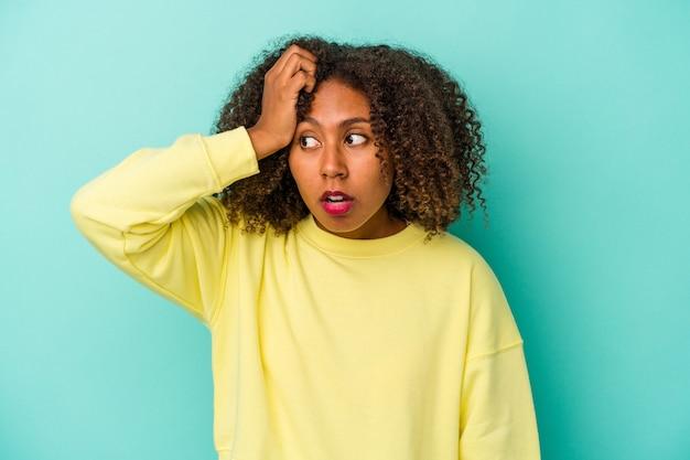 Jonge afro-amerikaanse vrouw met krullend haar geïsoleerd op een blauwe achtergrond die geschokt is, herinnert ze zich een belangrijke vergadering.