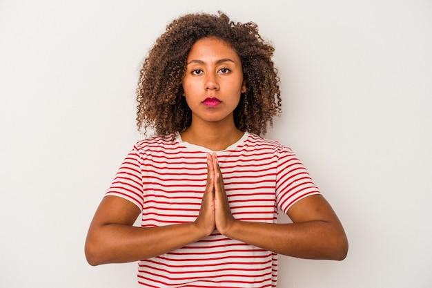 Jonge afro-amerikaanse vrouw met krullend haar geïsoleerd op een witte achtergrond bidden, tonen toewijding, religieuze persoon op zoek naar goddelijke inspiratie.