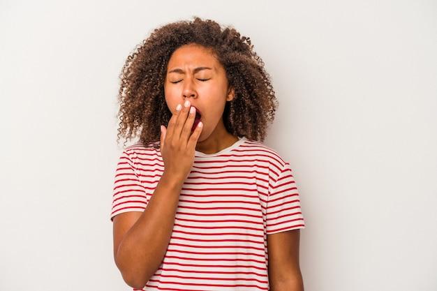 Jonge afro-amerikaanse vrouw met krullend haar geïsoleerd op een witte achtergrond geeuwen met een vermoeid gebaar voor mond met de hand.
