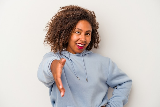 Jonge afro-amerikaanse vrouw met krullend haar geïsoleerd op een witte achtergrond hand uitrekken op camera in begroeting gebaar.