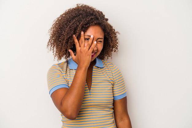 Jonge afro-amerikaanse vrouw met krullend haar geïsoleerd op een witte achtergrond knipperen naar de camera door vingers, beschaamd die betrekking hebben op gezicht.