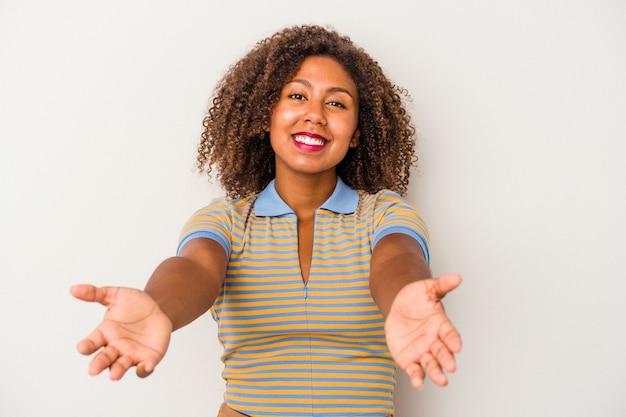 Jonge afro-amerikaanse vrouw met krullend haar geïsoleerd op een witte achtergrond met een welkome uitdrukking.