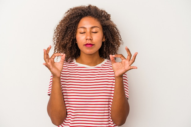 Jonge afro-amerikaanse vrouw met krullend haar geïsoleerd op een witte achtergrond ontspant na een zware werkdag, ze voert yoga uit.