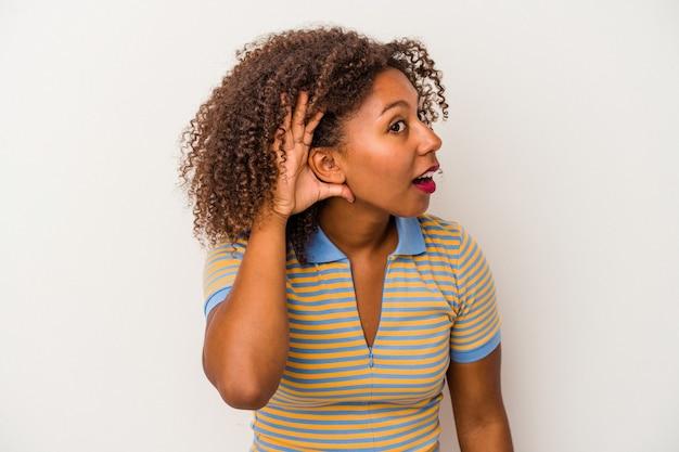 Jonge afro-amerikaanse vrouw met krullend haar geïsoleerd op een witte achtergrond probeert te luisteren naar een roddel.