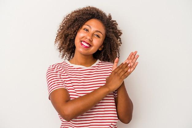 Jonge afro-amerikaanse vrouw met krullend haar geïsoleerd op een witte achtergrond voelt zich energiek en comfortabel, wrijft zelfverzekerd over de handen.