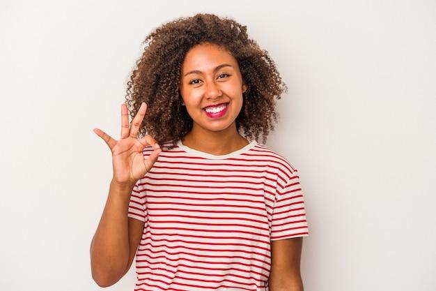 Jonge afro-amerikaanse vrouw met krullend haar geïsoleerd op een witte achtergrond vrolijk en zelfverzekerd weergegeven: ok gebaar.