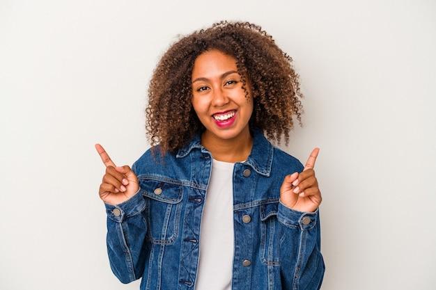 Jonge afro-amerikaanse vrouw met krullend haar geïsoleerd op een witte achtergrond, wijzend naar verschillende kopieerruimten, een van hen kiezend, tonend met de vinger.