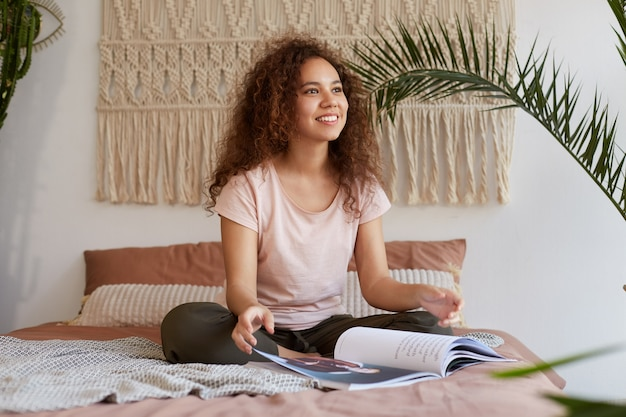 Jonge afro-amerikaanse vrouw met krullend haar, zit op het bed en kijkt dromerig weg, glimlacht en leest een nieuw reismagazine, vertegenwoordigt aanstaande reizen.