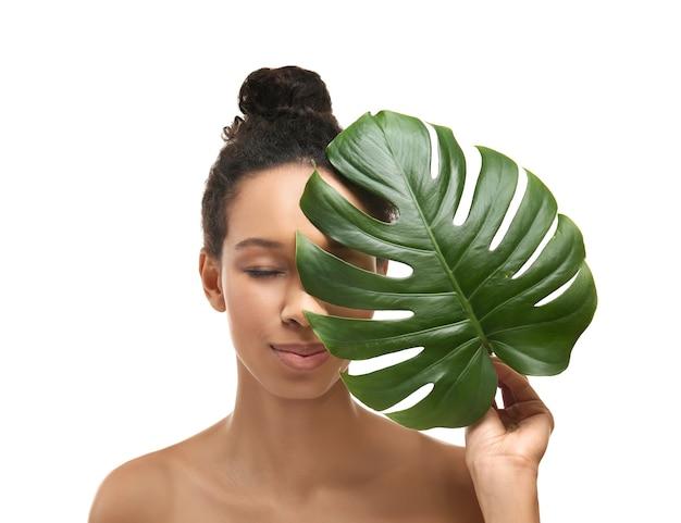 Jonge afro-amerikaanse vrouw met tropisch blad